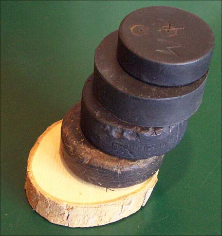 Top - Child's Rubber Puck c.1940s, Vulcanized Rubber Puck c.1930, Well Used Rubber Puck c.1920, Multi-Layered Leather Puck c.1915, Bottom - Wooden Puck